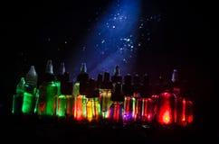Concept de Vape Nuages de fumée et bouteilles liquides de vape sur le fond foncé Effets de la lumière photographie stock libre de droits