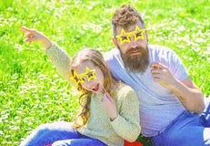 Concept de vedette du rock La famille dépensent des loisirs dehors Le père et la fille s'assied sur l'herbe au grassplot, fond ve images stock