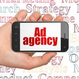 Concept de vente : Main tenant Smartphone avec l'agence de publicité sur l'affichage Photos libres de droits