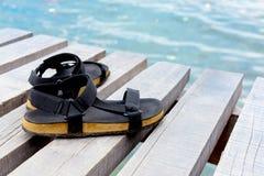 Concept de voyage avec des chaussures au-dessus d'en bois devant le landsc de mer Image stock