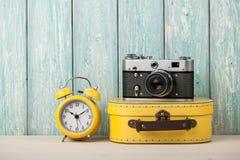 Concept de voyage avec la valise, l'appareil-photo de film et le réveil Images stock
