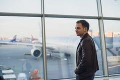 Concept de voyage avec le jeune homme dans l'intérieur d'aéroport avec la vue de ville et un vol plat par Image stock