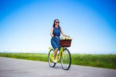 Concept de voyage - bicyclette de vintage d'équitation de femme dans la campagne photographie stock