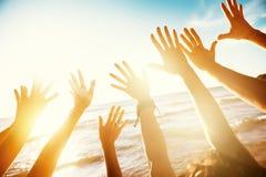 Concept de voyage d'amis avec les mains et la mer de coucher du soleil Photos stock