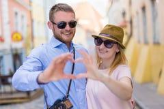 Concept de voyage et d'amour - jeune couple tenant des mains dans la forme de Photo stock