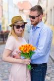 Concept de voyage et d'amour - jeune homme donnant des fleurs à son girlfr Photographie stock