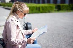 Concept de voyage et de vacances - jeune femme tenant la séance de touristes de carte en parc images libres de droits