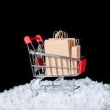 Concept de winterverkoop Het boodschappenwagentje met document zakken in sneeuw is Stock Foto's