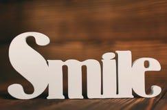 Concept de Word, de sourire et de motivation - texte de sourire sur le fond en bois Images stock