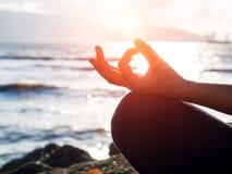Concept de yoga Pose de pratique de lotus de main de femme de plan rapproché sur la plage au coucher du soleil Photos stock