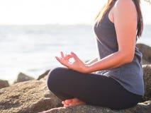 Concept de yoga Pose de pratique de lotus de main de femme de plan rapproché sur la plage au coucher du soleil Photo libre de droits