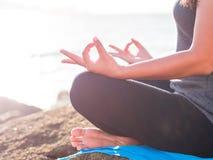 Concept de yoga Pose de pratique de lotus de main de femme de plan rapproché sur la plage au coucher du soleil Photographie stock