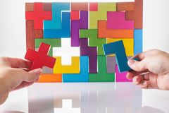 Concept of decision making process, logical thinking. Logical tasks. Conundrum, find the missing piece of the proposed. Hand holdi. Ng wooden puzzle element Stock Photos