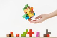 Concept of decision making process. Logical thinking. Logical tasks. Conundrum, find the missing piece of the proposed. Hand holding wooden puzzle element Stock Photo