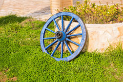 Concept of decor for garden - wooden wheel on a background of green grass Royalty Free Stock Photo