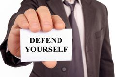 Man holding a card on which is written defend yourself. Concept of defending its interests royalty free illustration