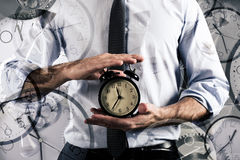 Concept of delay and time with clock. Businessman holds an alarm clock. Concept of delay and time Stock Images