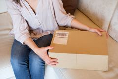 Concept of delivery and shipping and postal service. Concept of delivery, shipping and postal service .Woman holding open cardboard box or parcel at home royalty free stock photos