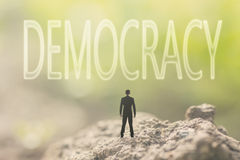 Concept of democracy. With a person stand in the outdoor and looking up the text over the sky in nature background royalty free stock image