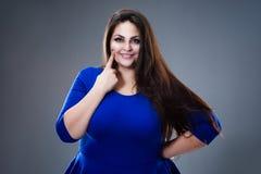 Concept dentaire de santé, grosse femme indiquant ses dents, plus le modèle de taille dans la robe bleue sur le fond gris images libres de droits