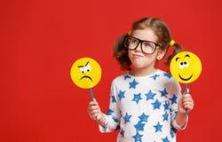 Concept des émotions du ` s d'enfants la fille d'enfant choisit entre un triste image libre de droits