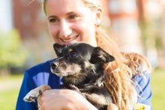 Concept des animaux familiers et du propriétaire heureux - la femme tient un chien dehors Image libre de droits