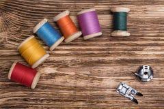 Concept des bobines de couleur avec des fils sur un conseil en bois Image stock