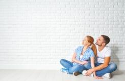 Concept des problèmes de logement d'hypothèque couples au mur vide photographie stock