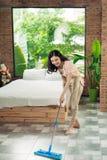 Concept des travaux domestiques et de ménage Plancher de nettoyage de femme avec le MOIS photographie stock