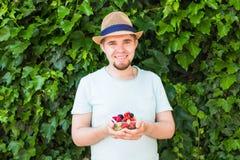 Concept des végétariens, de la nourriture crue et des régimes - la prise belle d'homme porte des fruits et des baies photo libre de droits