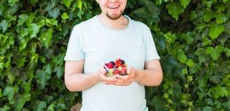 Concept des végétariens, de la nourriture crue et des régimes - la prise belle d'homme porte des fruits et des baies photographie stock libre de droits