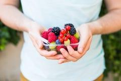 Concept des végétariens, de la nourriture crue et des régimes - le plan rapproché des mains du ` s de l'homme tiennent des fruits image stock