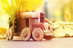 Concept design autumnal mood, yellow foliage on a background and a toy train. Fall October or November. Brightly colored maple leaves during autumn stock photos
