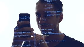 Double exposition of man programmer using smartphone with blue code on him. Concept development app for a smartphone.