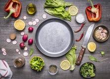 Concept die vegetarische die voedselingrediënten koken rond de pan met een ruimte van messenkruiden voor tekst op rustieke houten Stock Foto