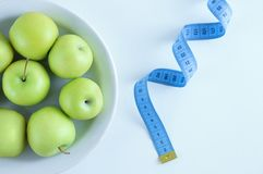 The concept of diet. Green apples on a white plate and meter. royalty free stock photography