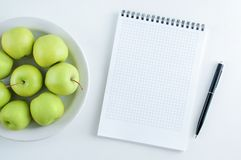 Concept of diet. Green apples on a white plate and a notebook with a pen. royalty free stock image