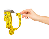 Concept of diet. Hand holding a fork with measuring tape on a wh Royalty Free Stock Photos