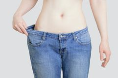Concept of diet and weight loss. Woman in big jeans on pastel gray background stock photos