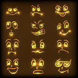 Concept of different facial expressions. Set of different facial expressions in shiny golden color on brown background Royalty Free Stock Images