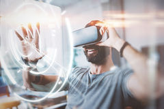 Concept of digital screen,connection and interfaces.Beraded hipster enjoyingvirtual reality glasses in modern design Royalty Free Stock Photography
