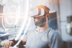 Concept of digital screen,connection and interfaces.Smiling hipster enjoyingvirtual reality glasses in modern design Stock Photos