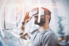 Concept of digital screen,connection and interfaces.Young coworker enjoyingvirtual reality glasses in modern design home Stock Photos
