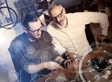 Concept of digital screen,virtual connection icon,diagram, graph interfaces.Two bearded coworkers making great time Stock Image