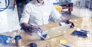 Concept of digital screen with virtual icon,diagram, graph and interfaces.Stylish bearded middle age man using laptop on Stock Image
