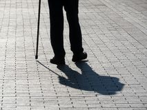 Silhouette of limping man walking with a cane, long shadow on pavement. Concept for disability, old age, blind person, dramatic life, diseases of the spine stock photos