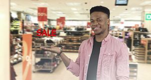 Concept of discount. African American black man in the shirt shows her hand a symbol of the sale on the store background. Shopping stock footage
