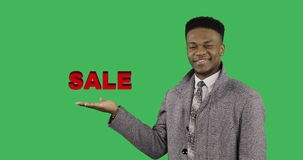 Concept of discount. African American black man in a winter coat shows her hand a symbol of the sale on green chroma key background stock video footage