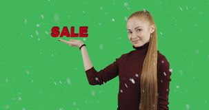 Concept of discount. A young woman with long red hair shows her hand a symbol of the sale in snowy weather on green chroma key background stock footage