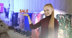 Concept of discount. A young woman with long red hair shows her hand a symbol of the sale on the store background. Shopping stock footage